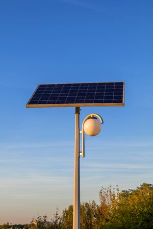 Park lamp powered by solar panel, sustainable, renewable green energy source from photovoltaic module.