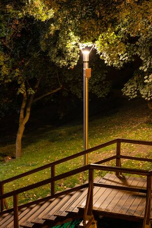 Wooden stairs illuminated by lamp in a park at night, city of Warsaw, Poland.