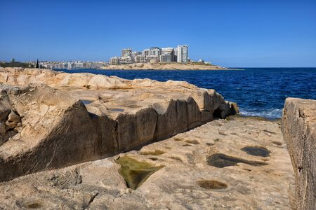 Valletta seaside in Malta, slipway (boat ramp or launch, boat deployer) to the sea carved in rocky shore with Sliema town on the horizon