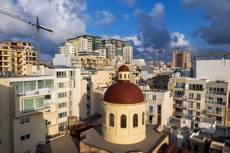 Sliema town in Malta, townscape with apartment buildings, condominiums and dome of Parish Church of Jesus of Nazareth.