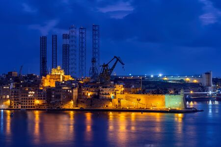 City skyline of Senglea (L-Isla, Civitas Invicta) in Malta at night, sea view with shipyard cranes in the background.