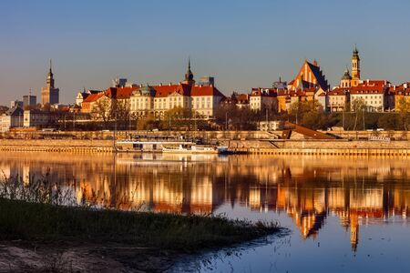 City skyline of Warsaw at sunrise, capital of Poland, Old Town river view with reflection in water Standard-Bild