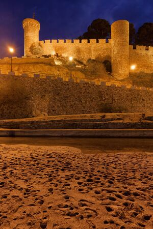Medieval stone wall with towers at night from a beach, part of the walled Vila Vella - the Old Town in Tossa de Mar in Catalonia, Spain.