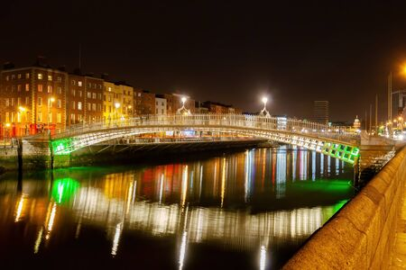 City of Dublin in Ireland, Ha Penny Bridge at night on River Liffey with reflections in water