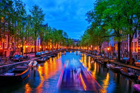 Evening by the canal in city of Amsterdam in Holland, the Netherlands, tranquil scenery in the Old Town, blurred shape of passenger cruise boat and lights reflected in water.