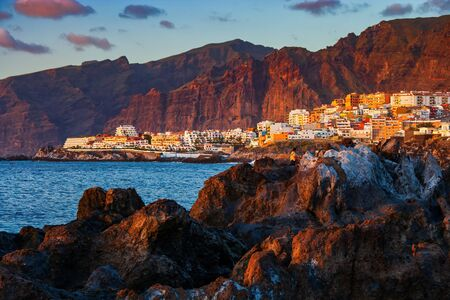 Tenerife island at sunset in Spain, view to Los Gigantes resort town and cliffs, scenic coastline of Canary Islands in the Atlantic Ocean