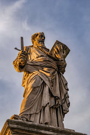 Saint Paul apostle statue holding a broken sword and a book on Ponte Sant Angelo bridge in Rome, Italy. Marble sculpture from 1464 by Paulo Romano at sunset