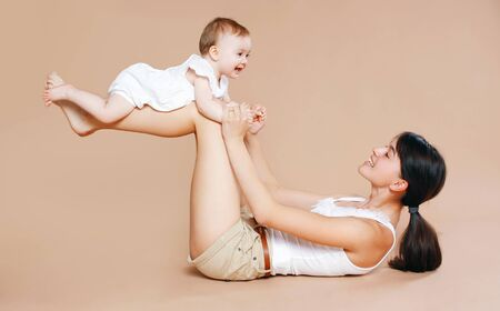 Mother holding baby, fun, exercise, leisure - concept photo