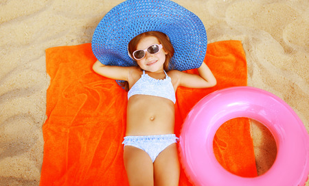Summer vacation sea concept, relax girl lying on the sand with beach set photo