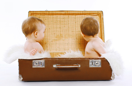 Twins sitting in a suitcase having fun, play, travel, family - concept photo