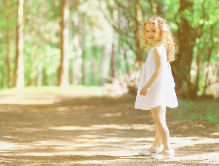Pretty curly little girl in summer sunny day photo