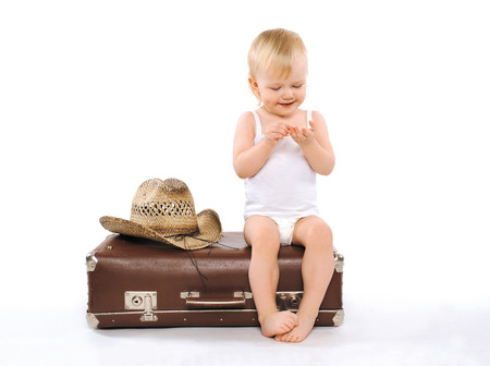 Child sits suitcase counts money on tours, travel, vacation - concept photo