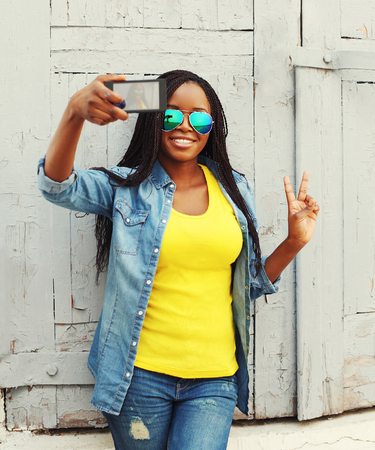 take a smile: Beautiful smiling african woman makes self-portrait on smartphone and having fun in city, view screen