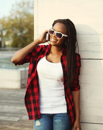 mujeres africanas: Hermosa mujer africana sonriente que habla en el teléfono inteligente en la ciudad, que lleva una camisa a cuadros rojo y gafas de sol