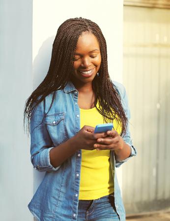 persone nere: Felice bella sorridente donna africana utilizzando smartphone in citt�