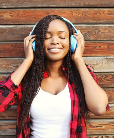 oir: Hermosa mujer africana sonriente con auriculares disfrutando escuchas música en la ciudad