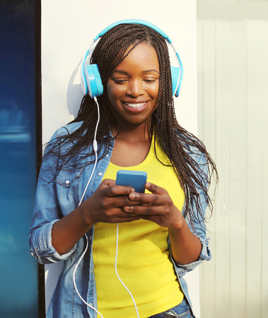 Beautiful smiling african woman with headphones listens to music and using smartphone in city