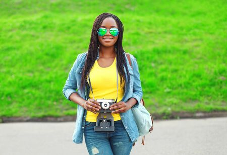 african women: Beautiful smiling young african woman with retro vintage camera in city park Stock Photo