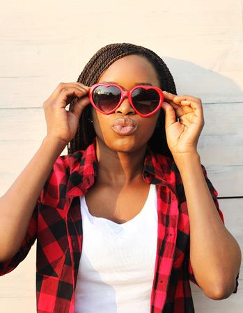mannequin africain: Belle jeune femme africaine dans des lunettes de soleil rouges amusent Banque d'images