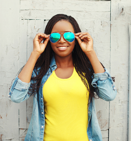charming: Portrait happy smiling african woman in colorful clothes and sunglasses Stock Photo