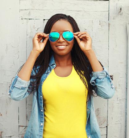 mannequin africain: Portrait heureux femme africaine souriant en vêtements colorés et des lunettes de soleil