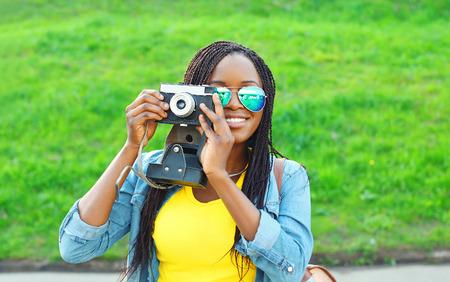 femme africaine: Portrait heureux femme africaine souriante avec appareil photo vintage r�tro dans le parc de la ville Banque d'images