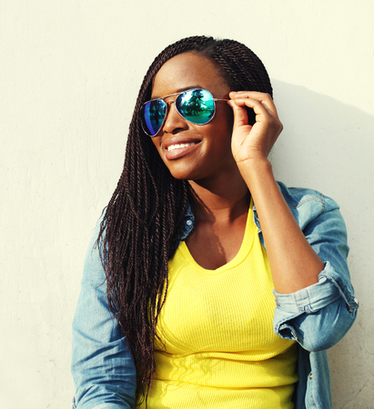 women posing: Portrait happy smiling african woman in colorful clothes and sunglasses in profile Stock Photo