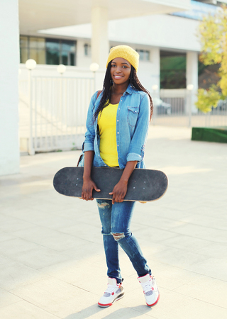 Pretty cool young african woman with skateboard in colorful clothes
