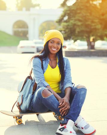 amarillo y negro: Mujer africana sonriente bastante fresco con el pat�n en ropa de colores al aire libre