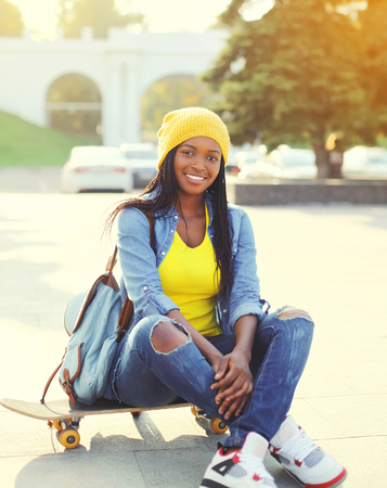 Pretty cool smiling african woman with skateboard in colorful clothes outdoors