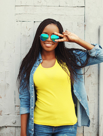 cool colors: Portrait pretty smiling african woman in colorful clothes and sunglasses having fun