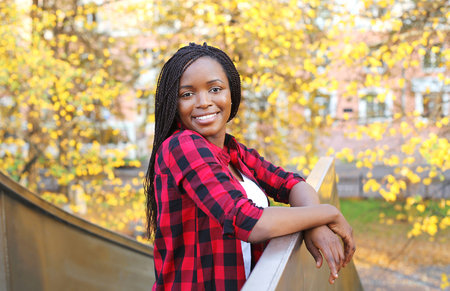 pretty: Pretty smiling young african woman wearing a red checkered shirt in city