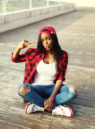 Fashion pretty young african woman having fun in city, wearing a red checkered shirt and cap