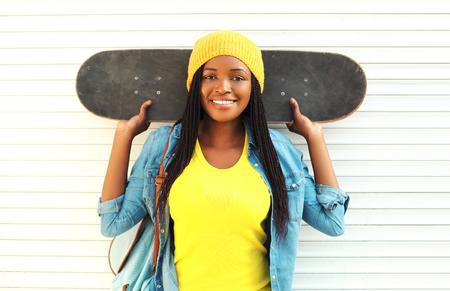 mannequin africain: Mode jolie jeune femme africaine souriante avec planche à roulettes dans des vêtements colorés sur fond blanc Banque d'images