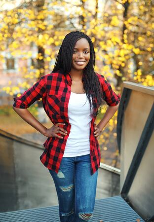 Pretty smiling african woman wearing a red checkered shirt in city Stok Fotoğraf - 47057007