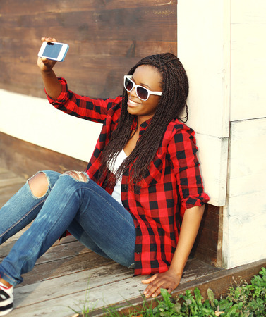 black: Fashion pretty smiling african woman makes self-portrait on smartphone and having fun in city