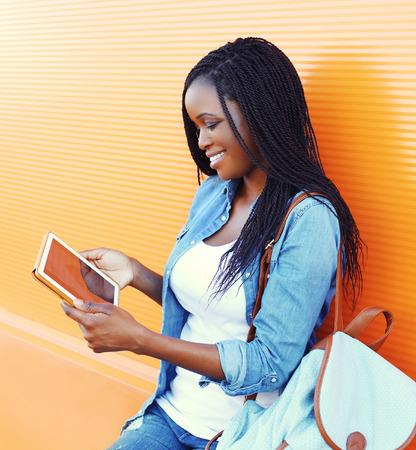 women black: Feliz mujer africana muy sonriente con tablet pc mira en la pantalla en la ciudad