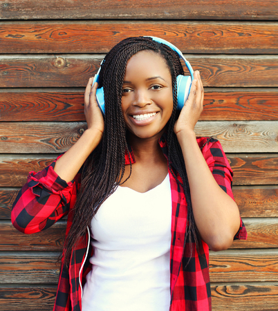 Beautiful smiling african woman with headphones listens to music and having fun in city over wooden background Banque d'images
