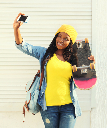 Beautiful smiling african woman with skateboard taking self-portrait picture on smartphone in city, wearing a colorful yellow clothes Standard-Bild