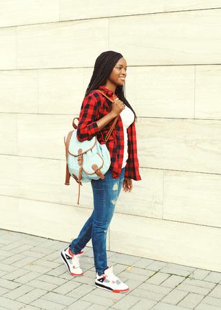 camisa: Mujer africana joven bastante sonriente con el morral que recorre en ciudad