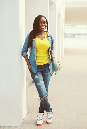 persone nere: Bella donna africana sorridente felice che indossa una camicia di jeans e zaino Archivio Fotografico