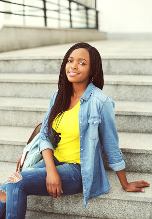 teen girl: Beautiful happy smiling african woman wearing a jeans shirt sitting resting on stairs