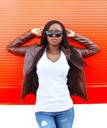 fashion model: beautiful african woman in city over red background Stock Photo