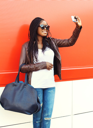 happy black woman: Beautiful smiling african woman taking self portrait picture on smartphone Stock Photo