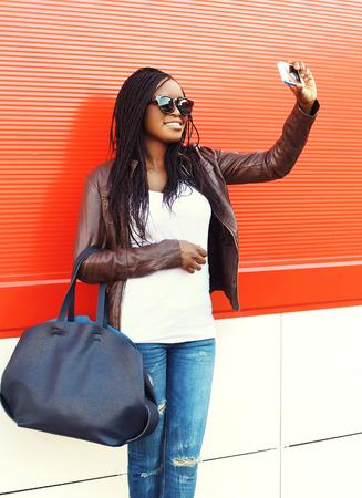 black girl: Schöne lächelnde afrikanische Frau, die Selbstportrait Bild auf dem Smartphone