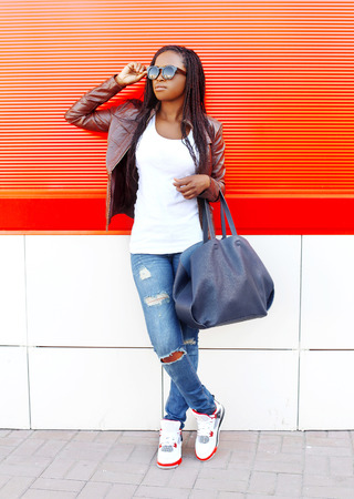 Beautiful african woman wearing leather jacket and sunglasses