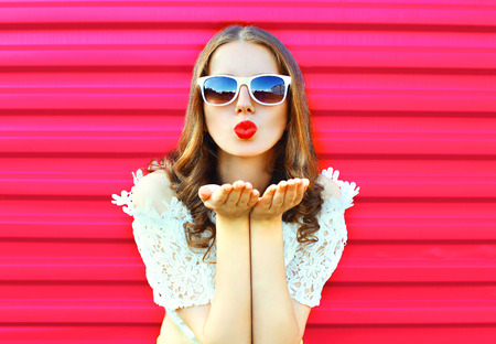 Woman in sunglasses sends an air kiss over colorful pink background