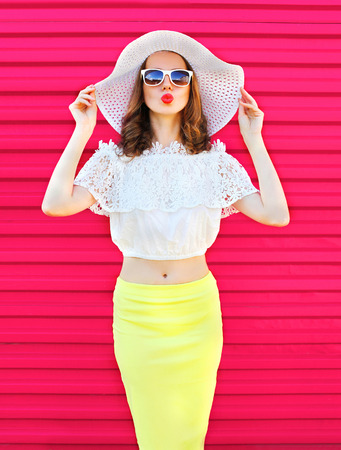 Fashion pretty woman in summer straw hat and skirt over colorful pink background