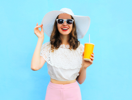 Fashion pretty smiling woman in straw hat with cup fruit juice over colorful blue background Standard-Bild