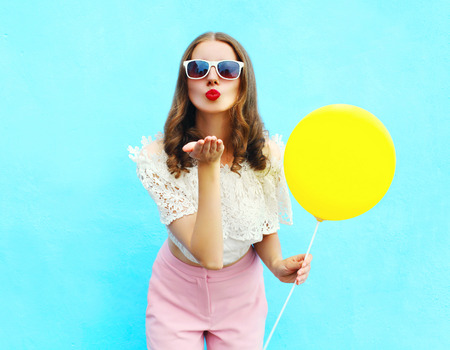Hübsche Frau in den Sonnenbrillen mit Luftballon sendet einen Luftkuß über bunten blauen Hintergrund Standard-Bild